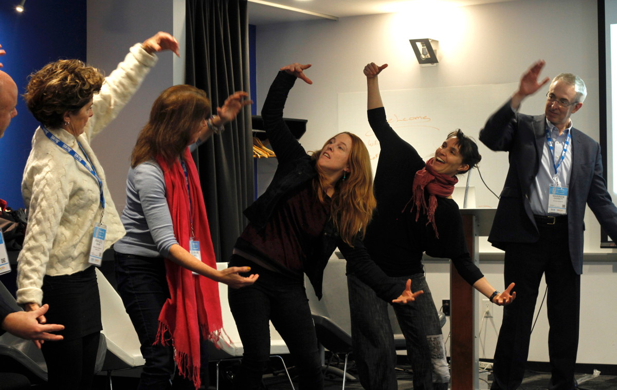 Workshop participants moving together with their arms wide open.