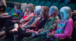 Des gens assis dans un théâtre et regardant / écoutant un atelier dirigé sur scène.