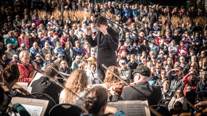 Conductor surrounded by musicians and audience members during an outdoor performance.