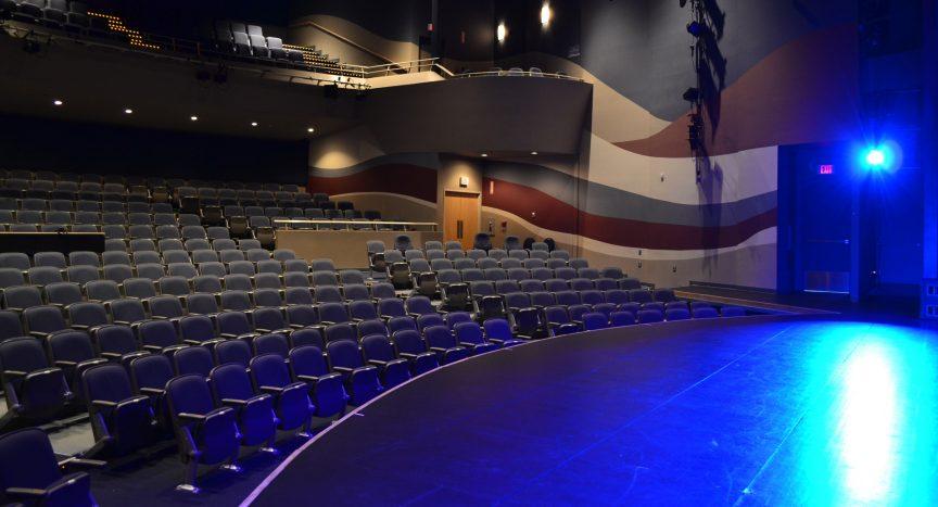 Salle de spectacle vide vue du côté jardin de la scène, sous un éclairage bleu.