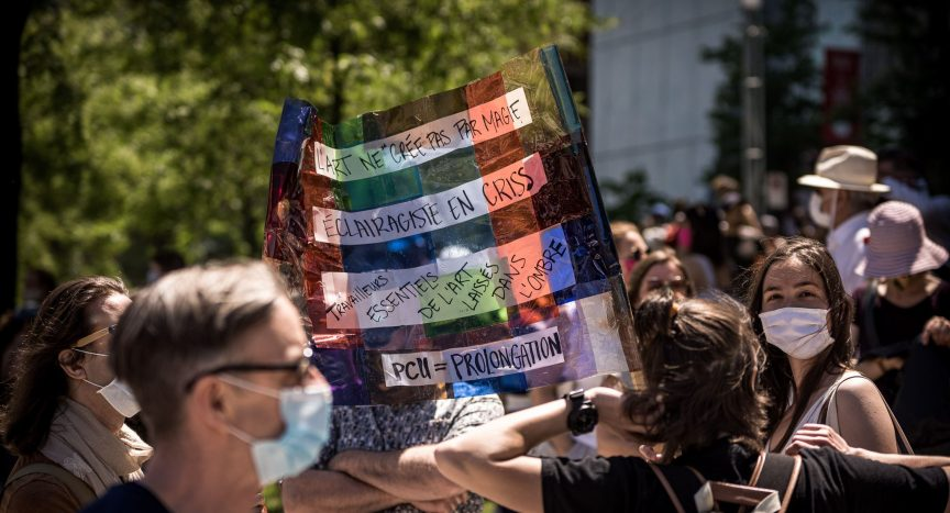 Cultural workers gathered in Montreal hold a colourful banner requesting an extension of the Canadian Emergency Response Benefit.