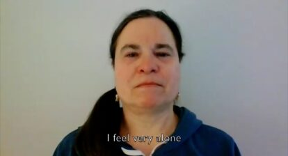 "Still from a video showing the face of a woman in front of a white wall. The caption reads ""I feel very alone""."