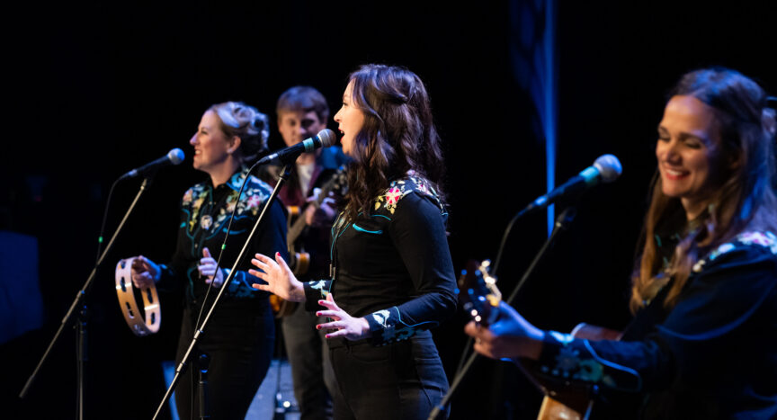 Three women sing and play joyously, along with a guitarist at the back. The side angle from the photo could lead to believe that the performers were close to one another, but physical distancing is implemented.