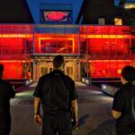 Ici, nous voyons trois techniciens qui regardent le Centre des arts et du patrimoine de l'Esplanade pendant la campagne #LightUpLive.