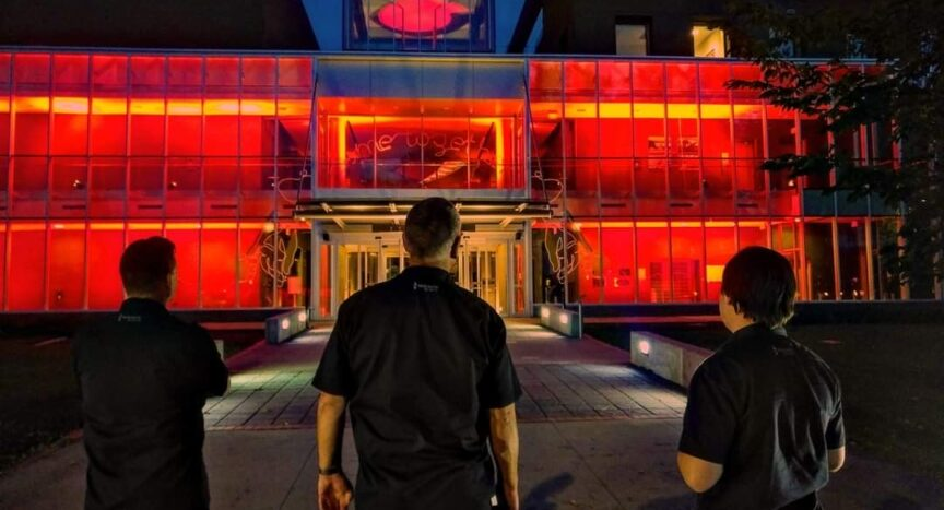 Photo of three technicians looking at the Esplanade Arts & Heritage Centre lit up in red lights