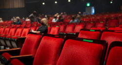 A nearly empty theatre, with seats marked for social distancing