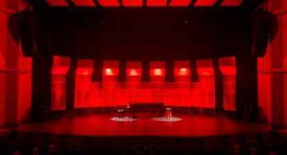 Photo of an empty theatre with a grand piano in the middle of the stage, lit up in red
