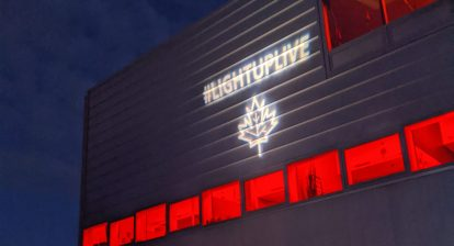 A building with red lights, and the LightUpLive logo