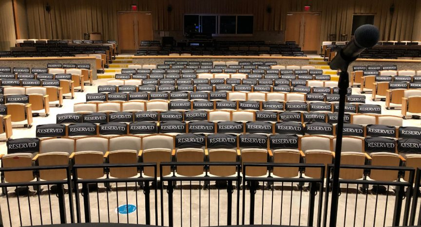 """View of the physically-distanced seating plan from the stage. Most seats are marked """"reserved"""" leaving a few safely distanced bubbles."""